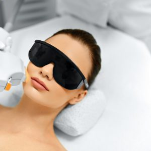 Skin Care. Young Woman Receiving Facial Beauty Treatment, Removing Pigmentation At Cosmetic Clinic. Intense Pulsed Light Therapy. IPL. Rejuvenation, Photo Facial Therapy. Anti-aging Procedures.